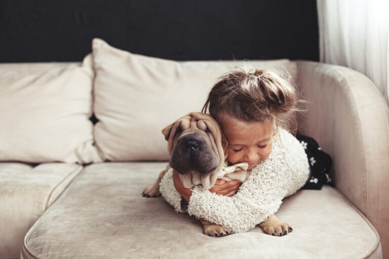 little girl hugging dog